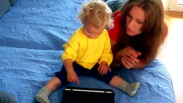 mujer y su niña hija jugando en la cama con tablet PC - vídeo