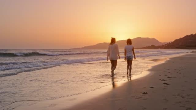 Woman and her teenage daughter walking on the beach at sunset and talking