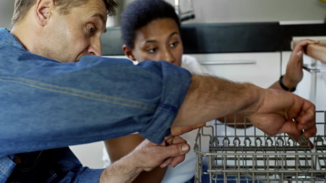 Woman and Male Plumber Inspecting Dishwasher Medium shot of mature male plumber in jeans shirt inspecting broken dishwasher and talking to black female homeowner appliance stock videos & royalty-free footage