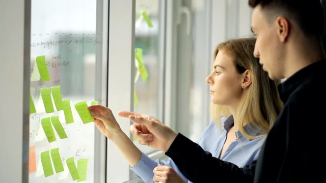 Woman and man are creating working process plan pointing video