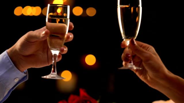 frau und mann klirren der gläser mit champagner, romantisches date, fest feier - champagner toasts stock-videos und b-roll-filmmaterial