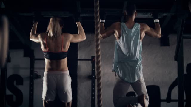 Woman and man doing chin-ups Rear view of a young strong woman and man doing chin-ups in gym. muscular build stock videos & royalty-free footage
