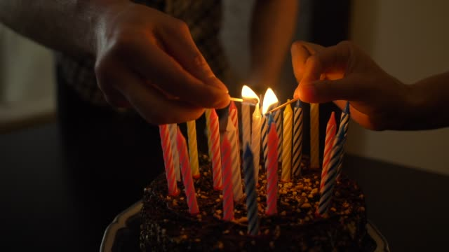 lezzetli doğum günü pastası kadın ve adam ışıklar mum. prepearing parti için - mum aydınlatma ürünleri stok videoları ve detay görüntü çekimi