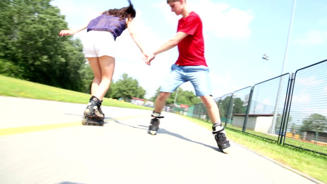 Woman and man rollerblading and performing in park on a beautiful warm day. video