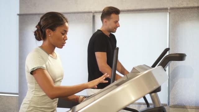 vídeos de stock e filmes b-roll de woman and man running on treadmill machine - aparelho de musculação