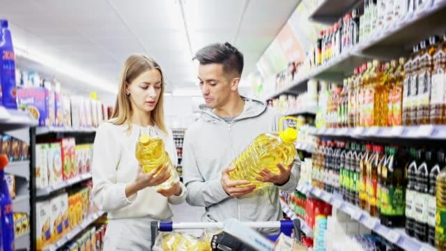 vrouw en mens die olie voor het koken tijdens familie het winkelen zoeken video