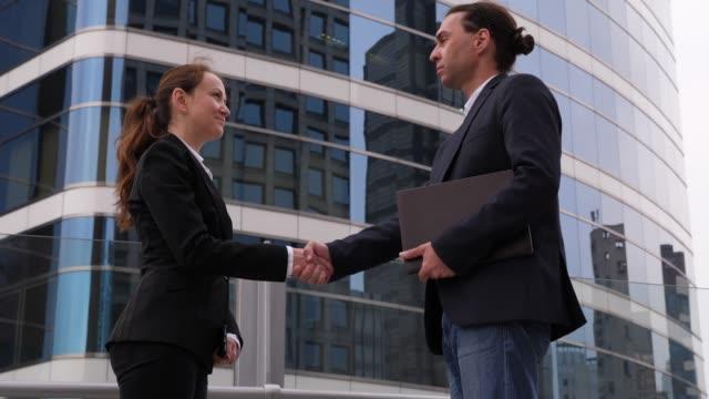 女人和男人在戶外握手,達成協議或達成諒解 - {{asset.href}} 個影片檔及 b 捲影像