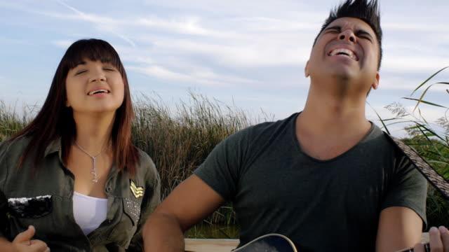 kvinna och man sjunga en låt med en gitarr - akustisk gitarr bildbanksvideor och videomaterial från bakom kulisserna