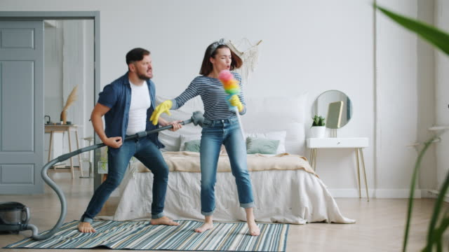 Woman and man singing in duster playing the guitar on vacuum cleaner in bedroom