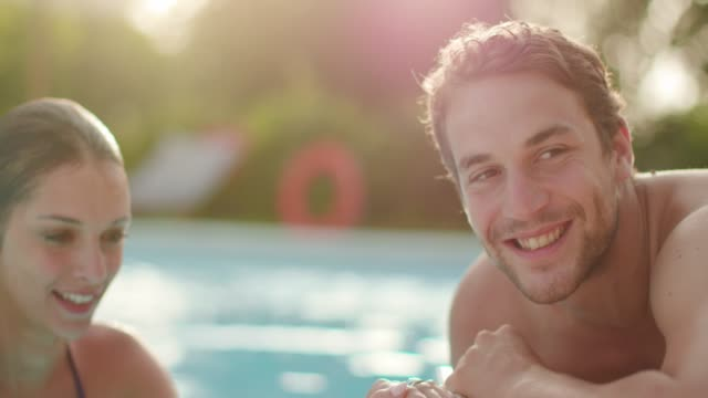Woman and man smiling near swimming pool water.Beautiful romantic couple relaxing and sunbathing at luxury rural villa house. Friends italian trip in Umbria.4k slow motion