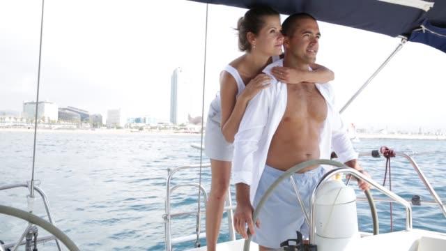 woman and man steering pleasure yacht, enjoying romantic sea travel - ster fragment pojazdu filmów i materiałów b-roll