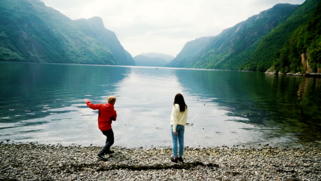 woman and man throwing stones into the fjord in norway - fiordo video stock e b–roll
