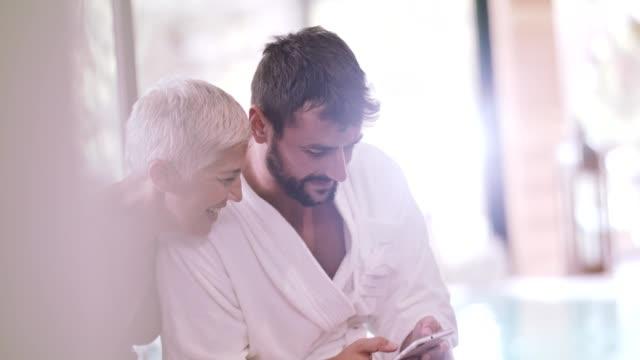 vidéos et rushes de femme et homme à l'aide de mobile au spa - peignoir