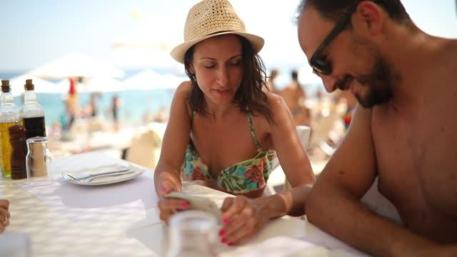 stockvideo's en b-roll-footage met vrouw en man met behulp van slimme telefoon in het restaurant - mid volwassen vrouw