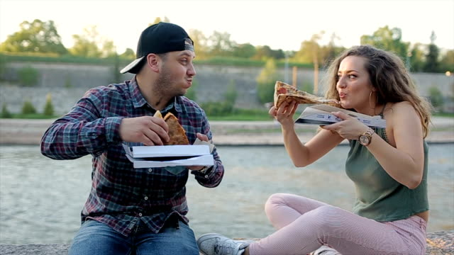 vídeos de stock e filmes b-roll de woman and men friends eating pizza outdoors and laughing - corpulento