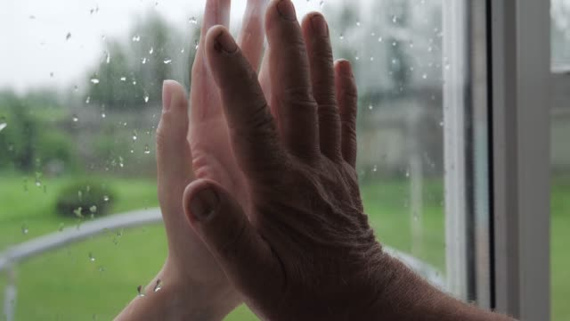 woman and old man touch palms of their hands through glass window closeup - hand on glass covid video stock e b–roll