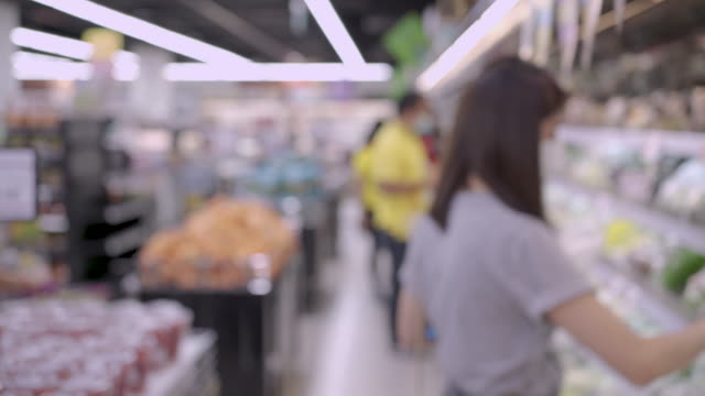 kvinna och människor i vit mask tittar på varor hylla i livsmedelsbutik i blur, livet under covid19 korona virusepidemi, mänsklig livsstil. lager upp på livsmedel medicin, folkhälsa bakgrund - dagligvaruhandel, hylla, bakgrund, blurred bildbanksvideor och videomaterial från bakom kulisserna