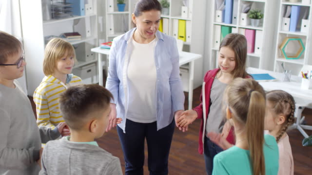 Woman and Six Kids Playing Funny Game in Circle Together High-angle medium shot of casually dressed young kids standing in circle with school counselor in her sunny office and playing brain teaser game together, watching each other attentively and laughing school counselor stock videos & royalty-free footage