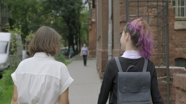 vídeos de stock, filmes e b-roll de mulher e menina do adolescente que andam junto, fundo do edifício da escola. - 16 17 anos