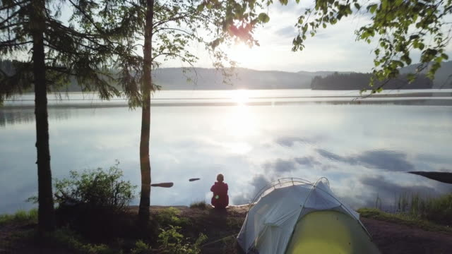 woman and tent inside forest by lake in norway - campeggio video stock e b–roll