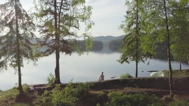 vídeos de stock e filmes b-roll de woman and tent inside forest by lake in norway - noruega