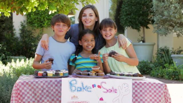 Woman And Three Children Having Bake Sale video