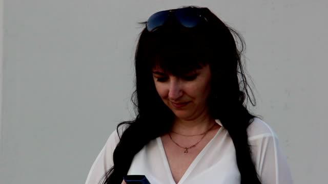 vídeos de stock e filmes b-roll de mulher cólera colocar o telefone, nervoso, depois de passar através de uma chamada telefónica - puxar cabelos