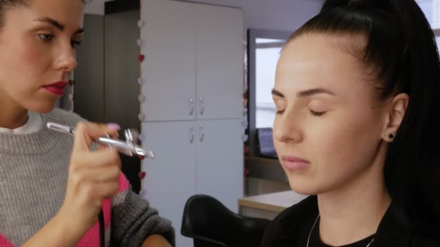 Woman applies airbrush concealer