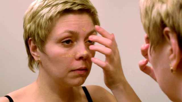 Woman applies makeup concealer foundation cream video