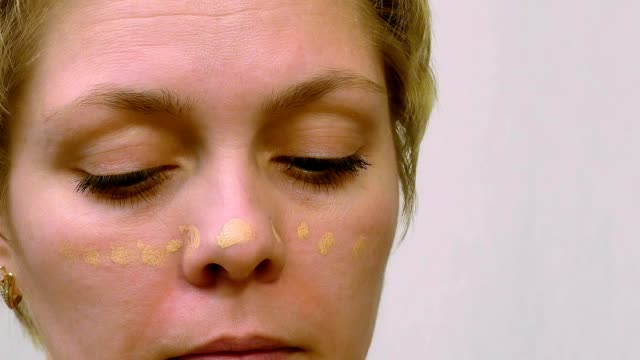 Woman applies makeup concealer foundation cream video