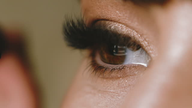 woman applies mascara on artificial lashes with brush macro CU, slow motion: brown eyed young woman applies mascara on long artificial lashes with brush on blurred background extreme close side view mascara stock videos & royalty-free footage