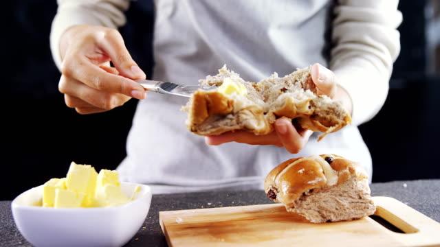 Woman applying butter over multigrain bun 4k video