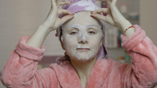 Woman applying cosmetic face mask in bathroom. Skincare spa. Facial mask