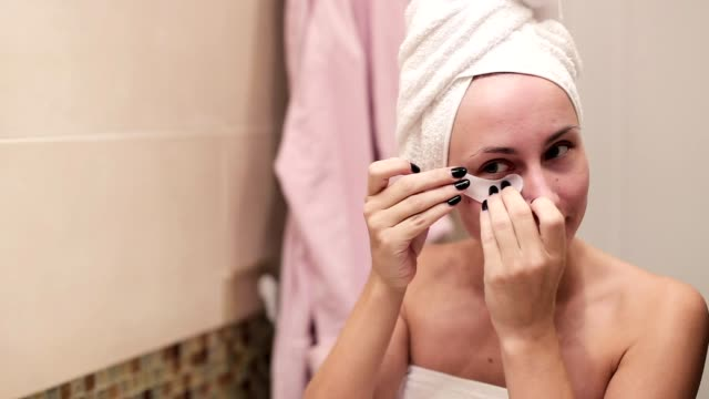 Woman applying hydrogel eye patches in the morning