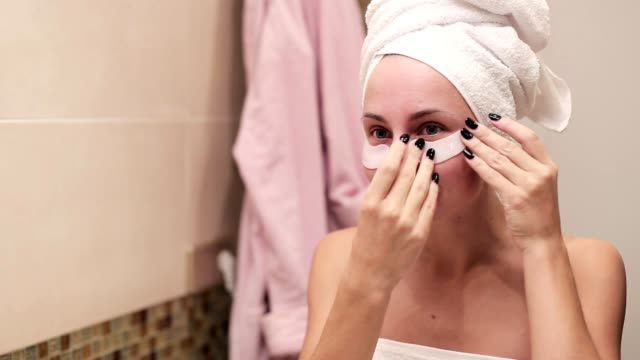 woman applying hydrogel eye patches in the morning - sotto video stock e b–roll