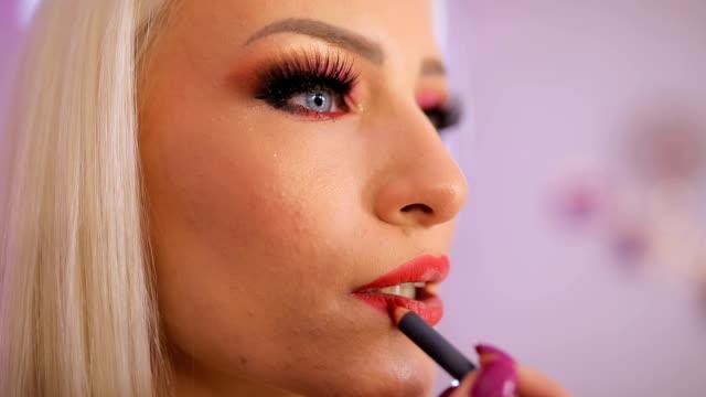 woman applying lipstick - rossetto rosso video stock e b–roll