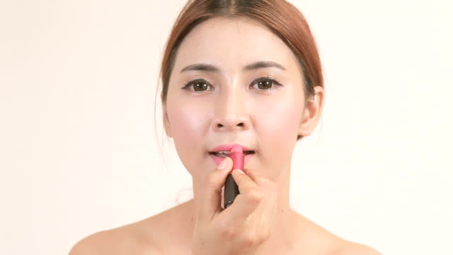 Woman applying lipstick Beauty asian woman applying lipstick on lips isolated on white lip liner stock videos & royalty-free footage