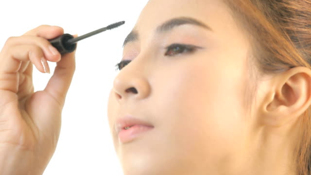 Woman applying mascara Young asian woman applying mascara on her long eyelashes isolated on white background mascara stock videos & royalty-free footage