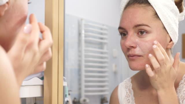 frau auftragen der maske creme auf gesicht im bad 4k - ausgedörrt stock-videos und b-roll-filmmaterial