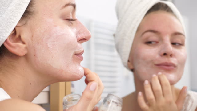 Woman applying mask cream on face in bathroom 4K Woman applying mask moisturizing skin cream on face looking in bathroom mirror. Girl taking care of her complexion layering moisturizer. Skincare spa treatment. 4K ProRes HQ codec lip balm stock videos & royalty-free footage