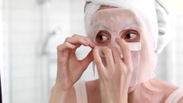 kvinna applicera masken på hennes ansikte i spegeln - japanese bath woman bildbanksvideor och videomaterial från bakom kulisserna