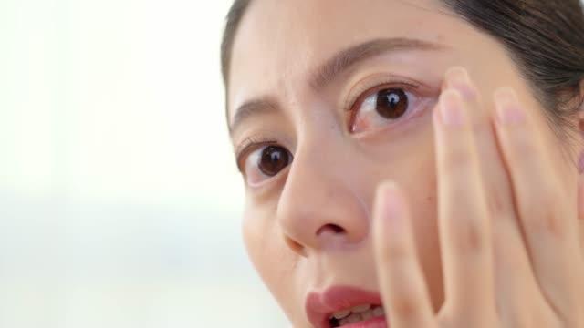 woman applying massage on her eyes video