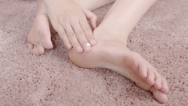 vídeos de stock e filmes b-roll de woman applying moisturizer cream on her foot.body care concept - feet hand