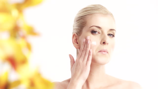 Woman applying moisturizer to her face video