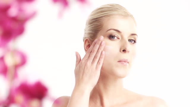 woman applying moisturizer to her face - sun cream stock videos & royalty-free footage
