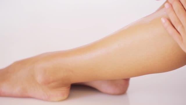 woman applying moisturizing cream to her leg - гладкая поверхность стоковые видео и кадры b-roll