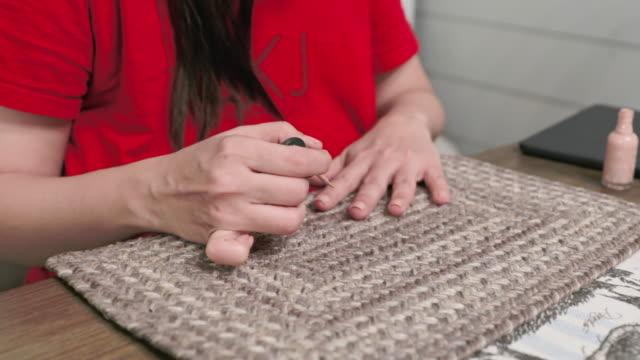 kvinna som tillämpar nail polska hemma - nagellack bildbanksvideor och videomaterial från bakom kulisserna