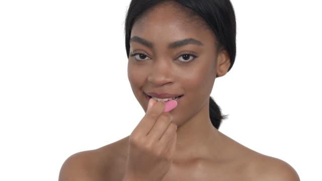 Woman applying pink lip balm. Lips makeup, cosmetic product usage Woman applying pink lip balm. Lips makeup, cosmetic product usage lip balm stock videos & royalty-free footage