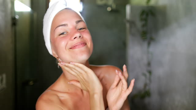 woman applying skincare lotion to face caring for skin in bathroom beautiful girl in towel happy smiling doing morning hygiene - woman face video stock e b–roll