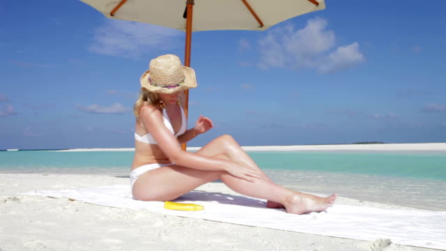 Woman Applying Sun Lotion On Beach Holiday video
